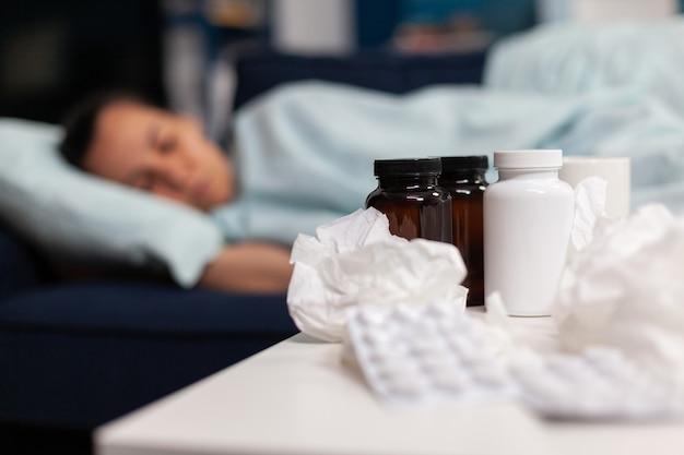 Feche de comprimidos de medicação e guardanapos para mulher doente dormindo no sofá, tomando drogas e tratamento médico.