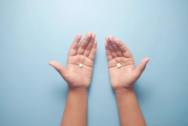 Feche de comprimidos médicos na palma da mão da criança