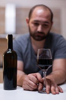 Feche de copo com vinho para o homem solitário na cozinha