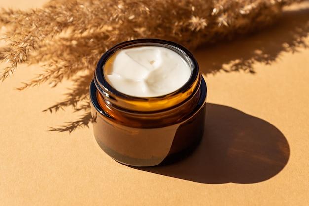 Feche de creme de colágeno em frasco de vidro e juncos de flores secas em fundo bege. produtos de beleza para cuidados com a pele e corpo