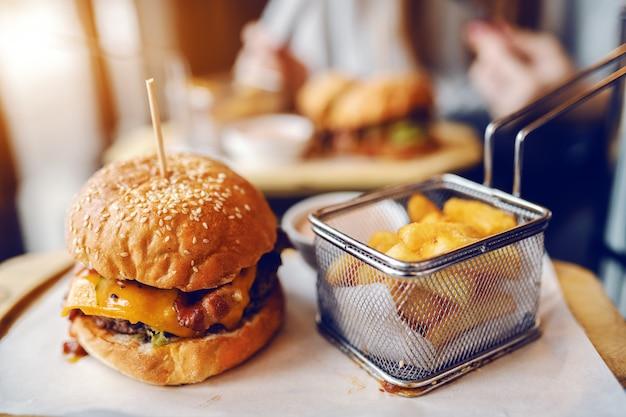 Feche de delicioso hambúrguer e batatas fritas no prato.