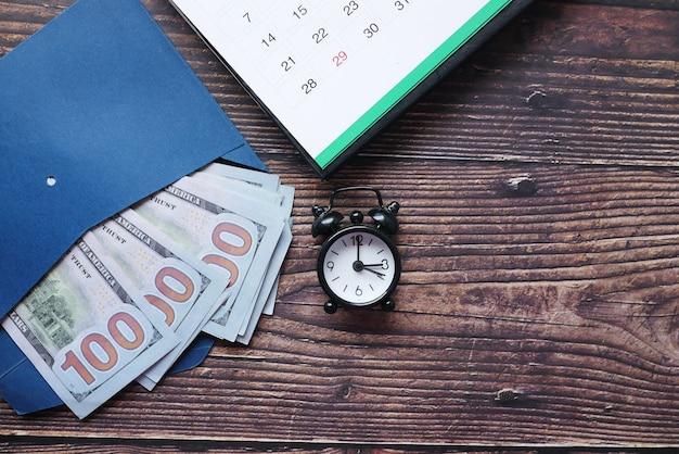 Feche de dinheiro em um calendário de envelope e um relógio antigo na mesa