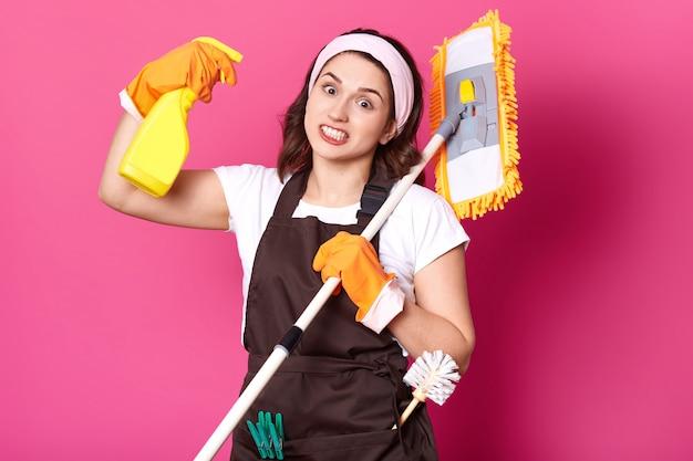 Feche de diversão jovem dona de casa em luvas laranja, avental marrom, camiseta branca, faixa de cabelo. mulher governanta atira do frasco de spray com líquido mais limpo, doente e cansado de fazer tarefas. conceito de higiene