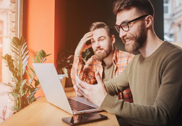 Feche de dois amigos sentados à mesa e olhando para a tela do laptop. um deles emocionalmente explica algo ao amigo enquanto o segundo homem está apenas ouvindo. cortar vista.