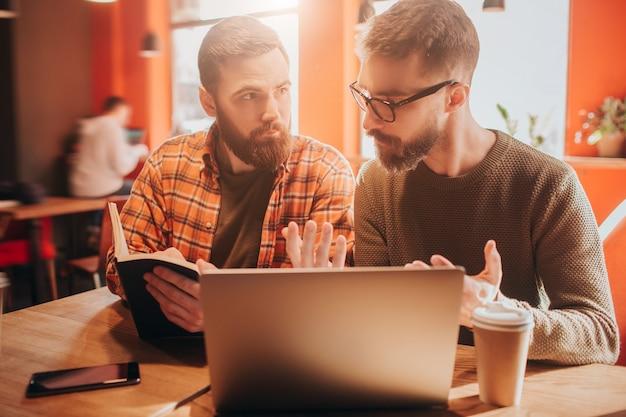 Feche de dois homens barbudos sentados juntos em um pequeno café. o cara da direita está explicando algo para o cara da direita, segurando um livro. eles parecem ocupados e concentrados.