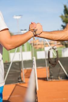 Feche de dois jogadores de tênis profissionais, segurando as mãos sobre a rede de tênis antes da partida.
