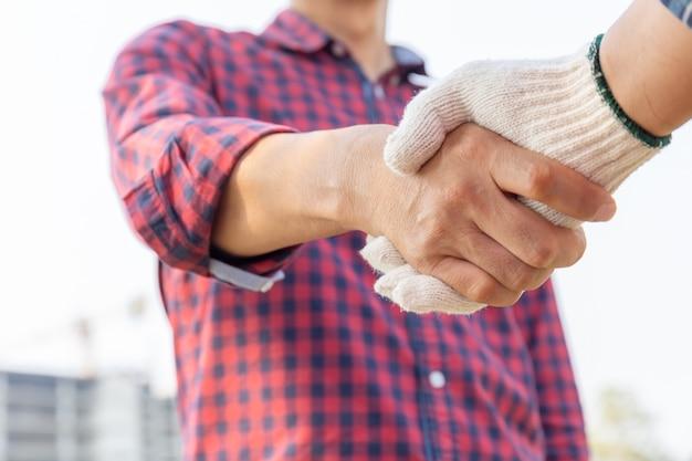 Feche de engenheiro e trabalhador aperto de mão com canteiro de obras turva, conceito de sucesso