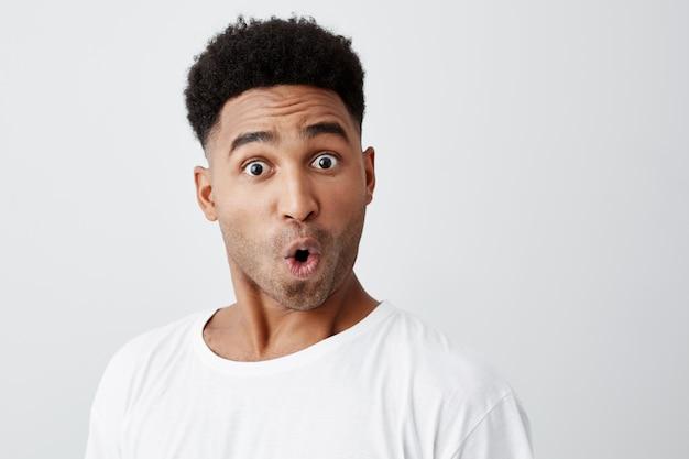 Feche de engraçado bonito jovem de pele escura com corte de cabelo afro em elegante camiseta branca, olhando na câmera com as sobrancelhas levantadas e expressão do rosto surpreso.