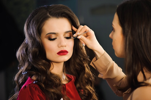 Feche de estilista profissional, alongamento de cílios para cliente do sexo feminino em um salão de beleza.