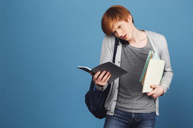Feche de estudante do sexo masculino gengibre bonito jovem em roupas casuais cinza com mochila segurando livros nas mãos, falando no telefone com o amigo, tentando entender a caligrafia no caderno.