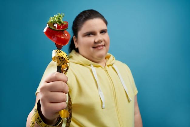 Feche de fatias frescas misturadas de tomate, pepino, pimenta e salada no garfo que é embrulhado por fita métrica amarela e mantendo a jovem senhora morena gorda. conceito de dieta saudável equilibrada.
