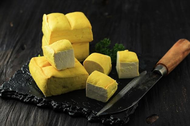 Feche de fresco feito cru requeijão de feijão amarelo bandung tofu corte cubo na mesa de madeira. conceito de refeição saudável vegana.
