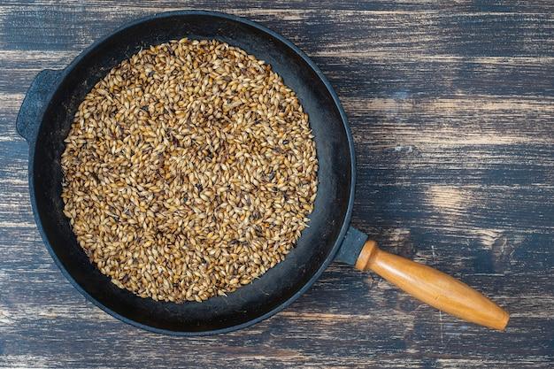 Feche de grãos de cevada torrada em uma frigideira de ferro fundido na mesa, vista superior. ingrediente para cerveja ou kvass