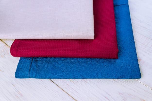 Feche de guardanapos de pano de cores bege, azuis e bordô na mesa de madeira branca rústica.