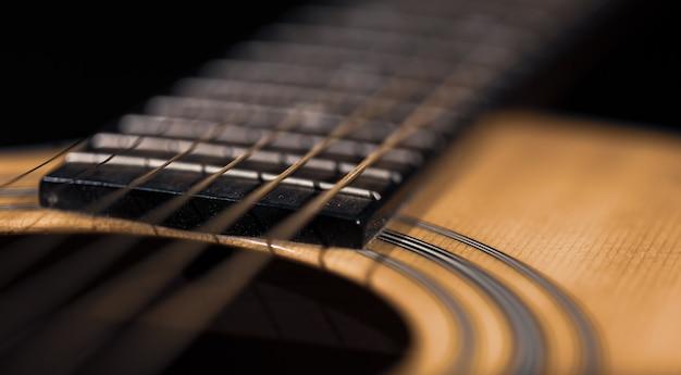 Feche de guitarra e cordas com profundidade de campo rasa, foco suave.