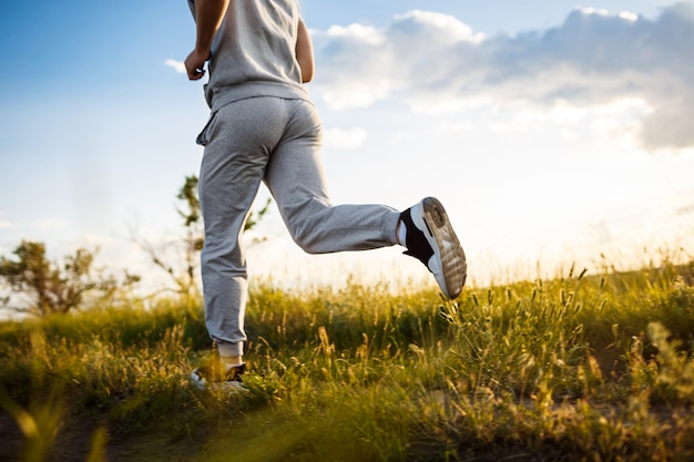 Feche de homem esportivo, movimentando-se em campo ao nascer do sol.