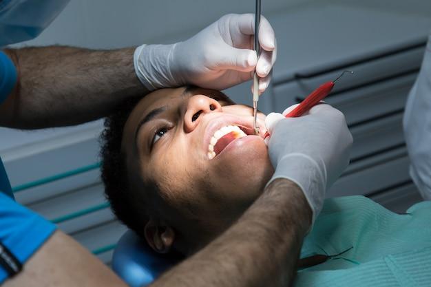 Feche de homem examinando a cavidade oral do jovem afro-americano trabalhando na clínica odontológica com assistente.