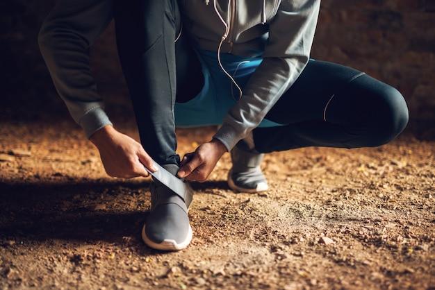 Feche de homem jovem ativo esportivo corredor no sportswear, amarrando o sapato de velcro lá fora.