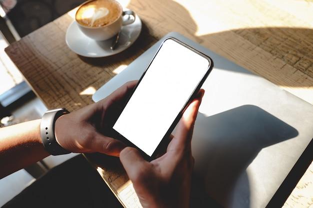 Feche de homem usando produtos de ordem de telefone celular em branco para fazer compras on-line dentro do café.