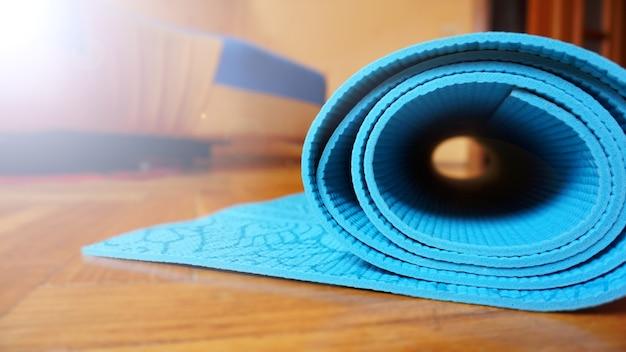 Feche de ioga, tapete de fitness em casa em um rolo. suportes e acessórios para ioga, tapete azul-turquesa. conceito de estilo de vida saudável
