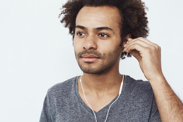 Feche de jovem africano, ouvindo música em fones de ouvido.