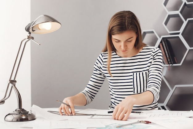 Feche de jovem bonito feminino designer feminino sério com longos cabelos escuros em elegantes roupas listradas. trabalhando no novo projeto de equipe usando régua e caneta.