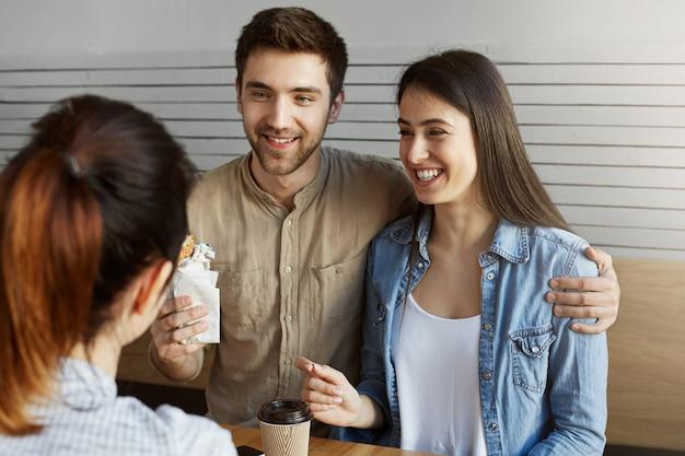 Feche de jovem casal de estudantes sentados na cantina após o estudo, falando sobre graduação e planos para o futuro. bonitão, abraçando a namorada.
