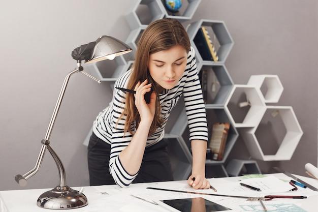 Feche de jovem designer magra linda com cabelos escuros na camisa listrada e calça jeans preta, trabalhando em casa, procurando no tablet digital, procurando exemplos de trabalho dos clientes.