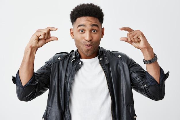 Feche de jovem estudante de pele escura linda com penteado afro em camiseta branca sob jaqueta de couro preta gesticulando com as duas mãos, olhando na câmera com expressão de rosto surpreso.