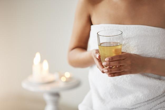 Feche de jovem na toalha, segurando o copo com chá verde no salão spa.