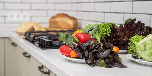 Feche de legumes e ervas para preparar salada na mesa da cozinha.