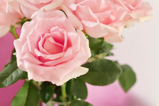Feche de lindo buquê de rosas em um vaso de vidro na mesa na sala de estar com espaço de cópia.