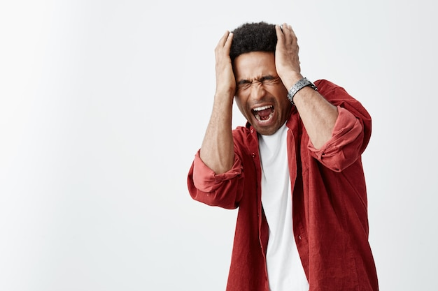 Feche de maduro infeliz ta-pele africano homem com penteado encaracolado em camisa casual branca e camisa vermelha, segurando a cabeça com as mãos, lutando de dor de cabeça depois da música alta na festa.