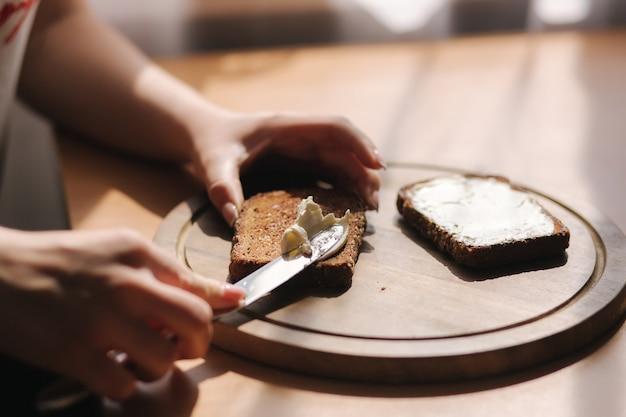 Feche de manteiga feminina o pão de centeio torrado com manteiga vegan. mulher torrada com manteiga em casa em