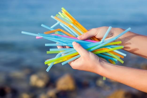 Feche de mão segurando palhas de plástico, poluindo a praia. conceito de poluição ambiental