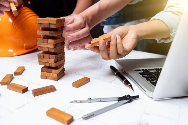 Feche de mãos ajudando a construir, planejamento, risco e estratégia em negócios, empresário e engenheiro de jogo colocando bloco de madeira em uma torre, luz do sol de cores quentes