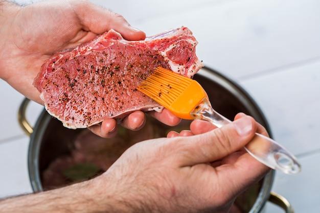 Feche de mãos de chefs apimentar a carne. caçarola com carne crua em um fundo branco.