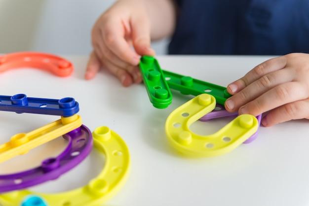 Feche de mãos de criança brincando de construtor de brinquedo de plástico brilhante. o bebê criativo cria novas formas. copie o espaço
