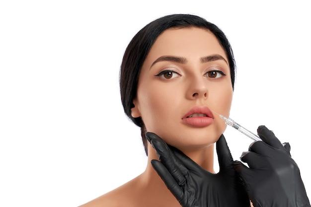 Feche de mãos de esteticista em luvas médicas, fazendo injeção de beleza para uma jovem encantadora. cosmetologista usando seringa durante procedimentos de beleza para cliente do sexo feminino.