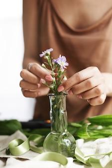 Feche de mãos de florista fazendo buquê de flores no local de trabalho.