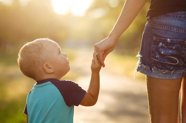 Feche de mãos de mãe e uma criança no ocaso. mãe e filho a passear no parque.