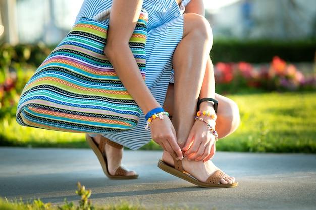 Feche de mãos de mulher, amarrando os sapatos de sandálias de verão aberto na calçada em tempo ensolarado.