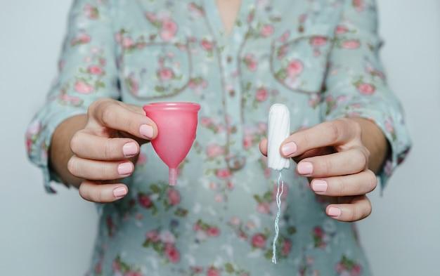 Feche de mãos de mulher comparando o tampão menstrual e o tampão. conceito de diferentes métodos de higiene íntima feminina.
