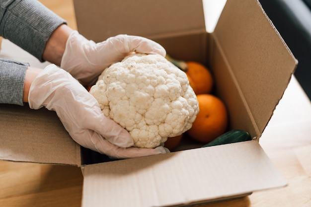 Feche de mãos de mulher em luvas caixa de embalagem com frutas e legumes frescos. supermercado online