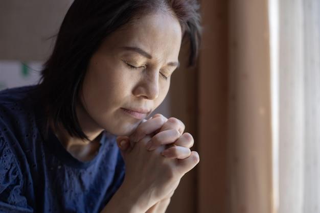 Feche de mãos de mulher orar na igreja.