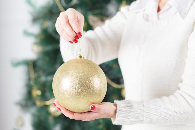 Feche de mãos de mulher segurando uma bola de natal goold. decoração, feriados e pessoas conceito