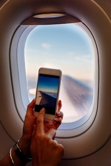 Feche de mãos de mulher tirando foto no avião. conceito de viagens.