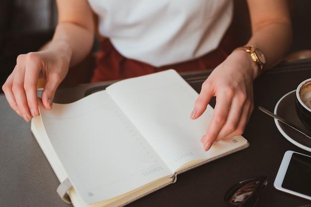 Feche de mãos femininas com o bloco de notas