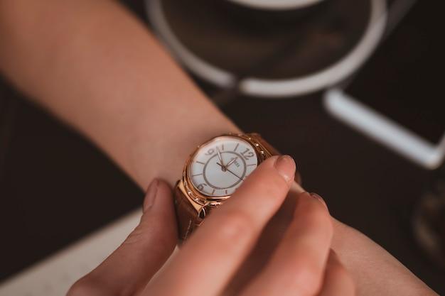 Feche de mãos femininas com relógio elegante
