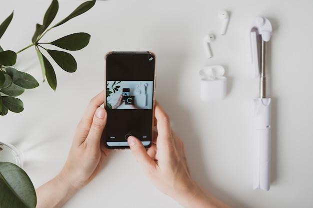 Feche de mãos femininas com smartphone na mesa branca